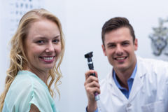 Female patient smiling with optometrist in background. At ophthalmology clinic Royalty Free Stock Image
