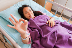 Female patient sowing cheerful ok hand sign. Female patient sowing her ok hand sign for cheerful Royalty Free Stock Images