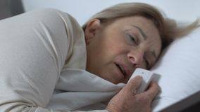 Female patient suffering from pain pushing call-button, needing help, hospital stock footage