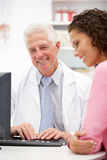 Female patient talking with senior doctor Stock Image