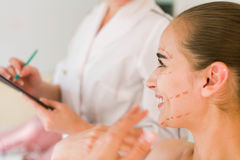 Female patient is talking and smiling with doctor. Royalty Free Stock Images