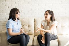 Female patient talking to therapist on sofa. Pretty young women talking to female therapist on sofa, sharing her issues during psychotherapy Royalty Free Stock Images