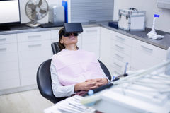 Female patient using virtual reality headset during a dental visit Stock Images
