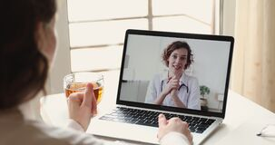 Female patient video calling woman doctor on laptop screen