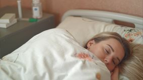 Female patient wakes up in a hospital bed stock photos