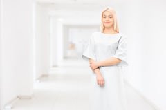 Female patient wearing hospital gown and posing in a hospital. Corridor stock photography
