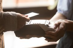 Female paying with credit card use NFC technology closeup hands royalty free stock image