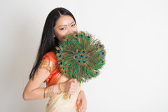 Female with peacock feather fan in Indian sari dress stock photo
