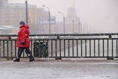 female pedestrians cross the bridge during the fallen wet snow royalty free stock photos