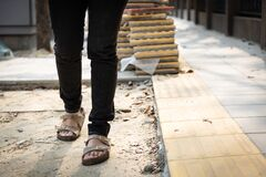 Free Female Pedestrians People Is Walking On A Footpath Walkway Under Construction And Stacked Cobblestone Block Or Renovation,damaged Royalty Free Stock Image - 170670356