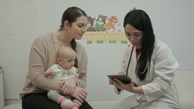 Female pediatrician doctor shows something on