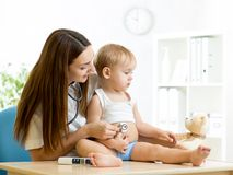 Female pediatrician examining of toddler kid with Royalty Free Stock Photography