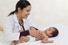 Female pediatrician holds newborn baby. Against white background stock images