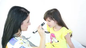 Female Pediatrician performing an eye exam on a female child stock video