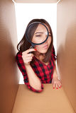 Female peeking into carton box looking through magnifying glass Stock Photo
