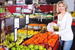 Female pensioner buying fresh fruits Royalty Free Stock Image