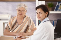 Female pensioner at doctors office. Looking at camera Royalty Free Stock Photo