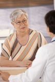 Female pensioner at doctors office. Listening to doctors explanation Stock Photos