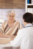 Female pensioner at doctors office. Looking at camera Royalty Free Stock Image