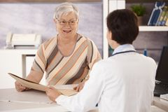 Female pensioner at doctors office. Listening to doctors explanation Royalty Free Stock Image