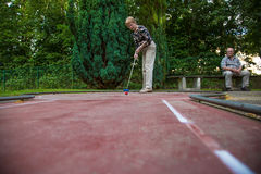 Female pensioner at the end of the minigolf court is preparing f Stock Image