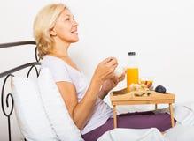 Female pensioner having  breakfast in bed Stock Photo