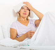Female pensioner laying with headache. Female pensioner laying in bed with headache royalty free stock photography