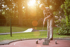 Female pensioner at a minigolf court hits a ball with an iron ra Stock Photo