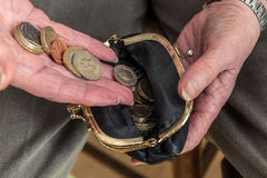 Female pensioner putting money into her purse. Pensioner counting money into her purse. British coins. Close up of hands. Poor pensioner concept Royalty Free Stock Photo