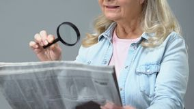 Female pensioner reading newspaper through magnifying glass, poor eyesight. Stock footage stock video