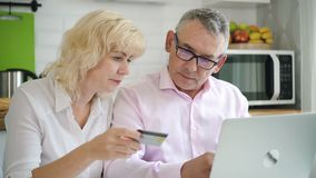 Female pensioner and senior man paying for online shopping in kitchen. stock video