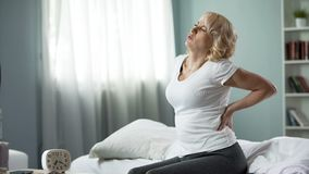 Female pensioner touching her back, suffering from pain, rheumatism symptom stock photo
