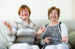 Female pensioners discussing something and laughing indoors Royalty Free Stock Photography