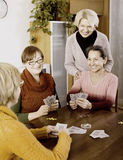 Female pensioners playing cards stock photography