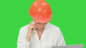 Female pensive architect using laptop and paper plan to check progress on a Green Screen, Chroma Key. stock footage