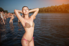 Female with perfect body stay in water and take sun; Stock Images