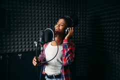 Female performer songs in audio recording studio. Female performer in headphones songs in audio recording studio. Musician listens composition, professional stock photography