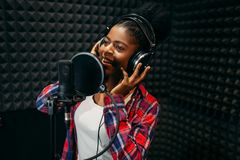 Female performer songs in audio recording studio. Female performer in headphones songs in audio recording studio. Musician listens composition, professional royalty free stock photo