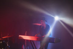 Female performer playing piano on illuminated stage Stock Photos