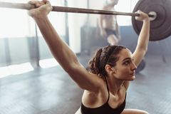 Female performing deadlift exercise with barbell royalty free stock photo