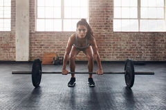 Female performing deadlift exercise with weight bar. Confident young woman doing weight lifting workout at gym Royalty Free Stock Image