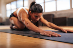 Female performing yoga on exercise mat at gym. Woman doing stretching workout on fitness mat, focus on hands, fitness female performing yoga on exercise mat at Stock Photo