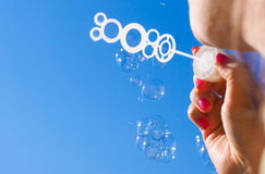 Female person blowing soap bubbles Stock Photography