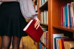 Female person at bookshelf in university library. Female person with book at the bookshelf in university library. Woman in knowledge depository, education stock photography