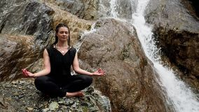 Woman meditation practicing yoga near waterfall stock footage