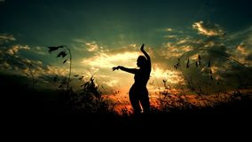 Female person dancing in evening steppe, silhouette in sunset background. Female person doing yoga in evening steppe, silhouette in sunset background. Concept stock image