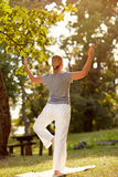 Female person doing body balance exercise in park, back view Royalty Free Stock Photo