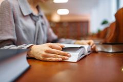Female person hands with book, university library. Female person hands with book in university library. Woman studying in knowledge depository, education stock photos