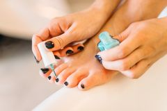 Female person hands with nail polish, pedicure. Procedure closeup. Nailcare treatment process Royalty Free Stock Image