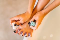 Female person hands with nail polish, pedicure. Procedure closeup. Nailcare treatment process Stock Photography